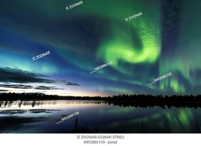 Northern lights reflecting in a forest lake, Lapland, Sweden