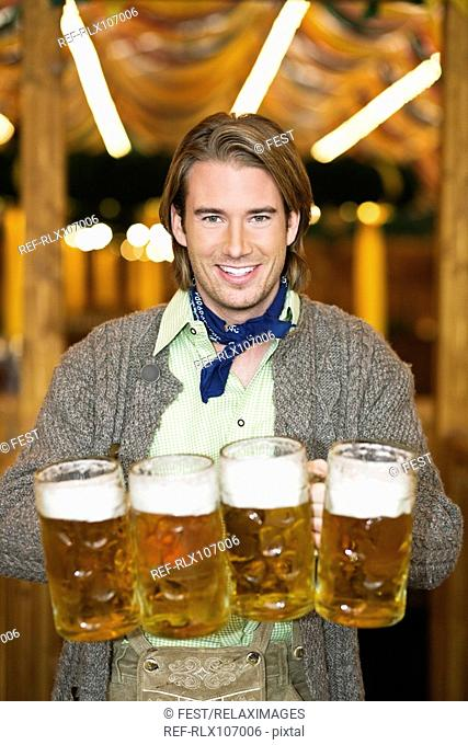 Waiter holding 4 Mass beer jugs at Oktoberfest, Munich, Germany