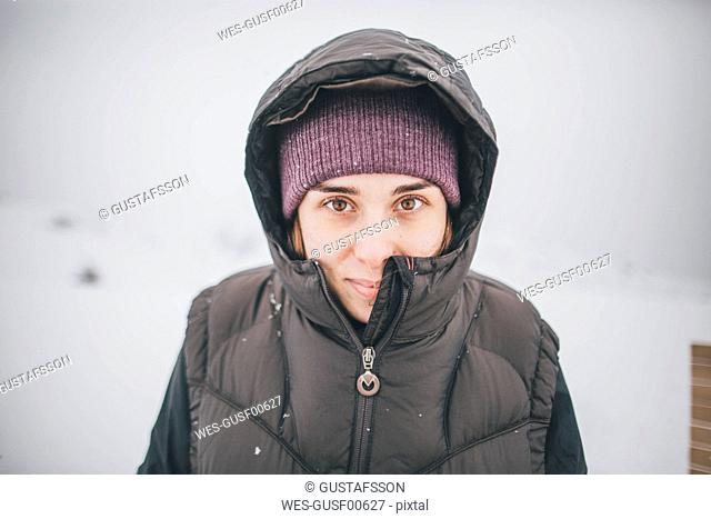 Austria, Kitzbuehel, portrait of smiling young woman in winter