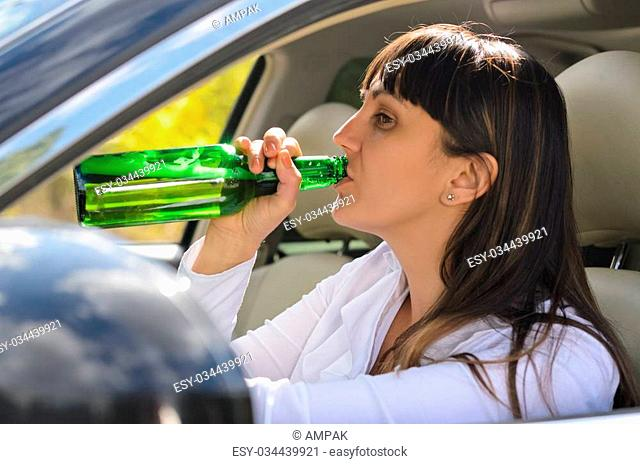 Alcoholic woman drinking and driving raising the bottle to her lips to take a swig as she steers the car, view through the side window