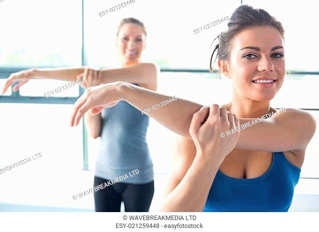 Two women stretching their arms