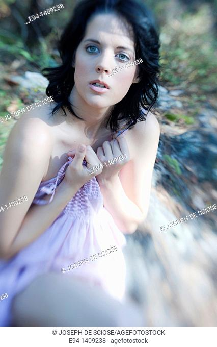 Portrait of a partially nude nineteen year old brunette woman looking away from the camera sitting on a rock in a forest setting covering herself with a dress