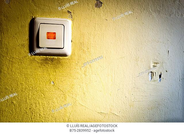 Power switch with a red light on yellow wall in a residential building. Neukölln, Berlin, Germany