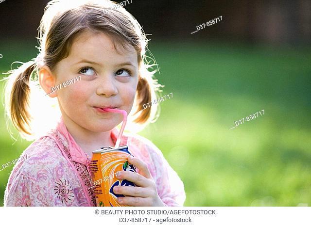 Little girl drinking soda in the garden