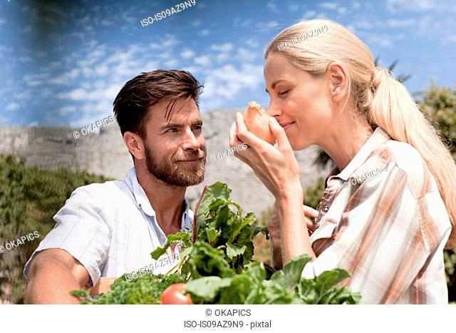 Mature couple in garden, woman smelling onion