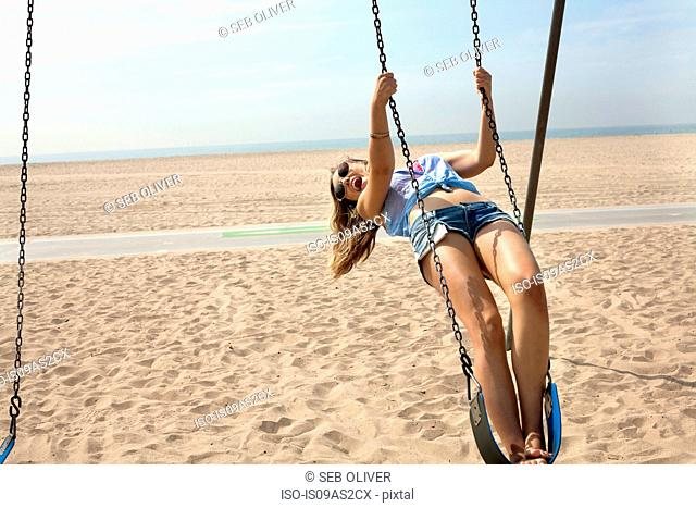 Young woman on beach, swinging on playground swing