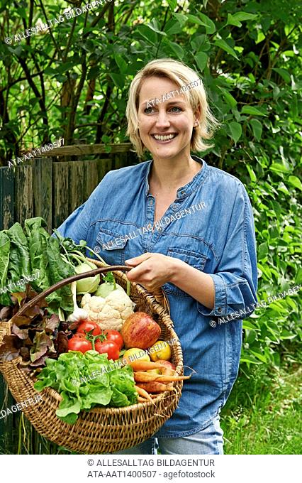 Woman with a basket full of fruits and vegetables