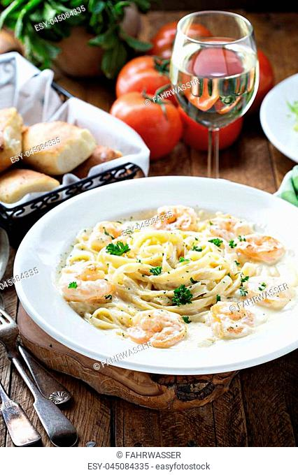 Creamy fettuccine alfredo with shrimp on wooden table