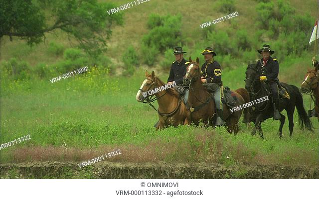 American 7th cavalry on horseback riding through countryside with regiment flag