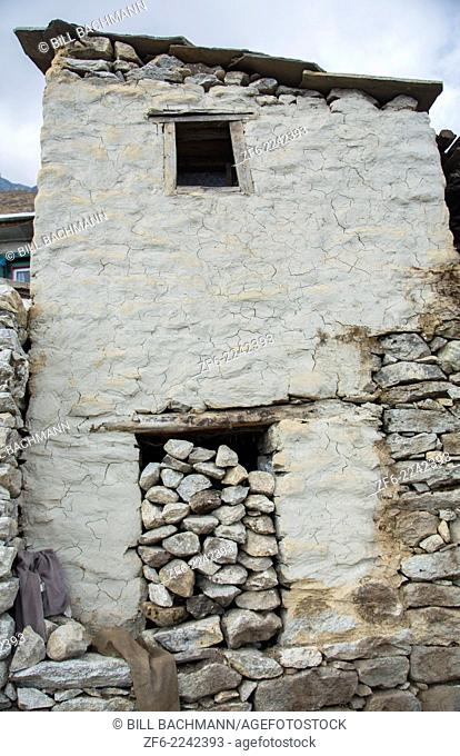 "Nepal What is called an """"old-style"""" Sherpa house with its doorway filled with rocks in the village of Khumjung, Solukhumbu, remote, Mt Everest, Himalayas"