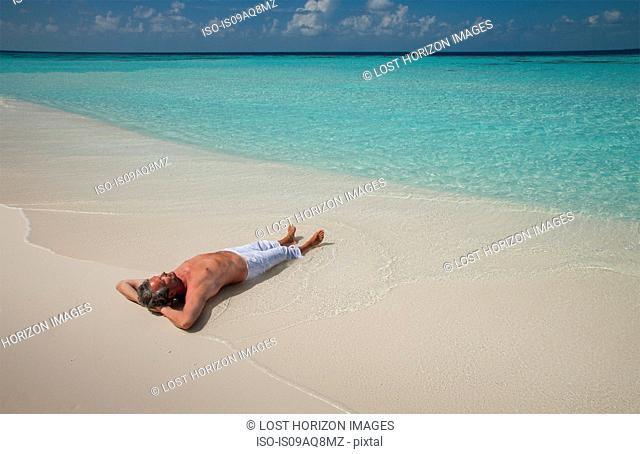 Senior man lying on sandy beach, Maldives