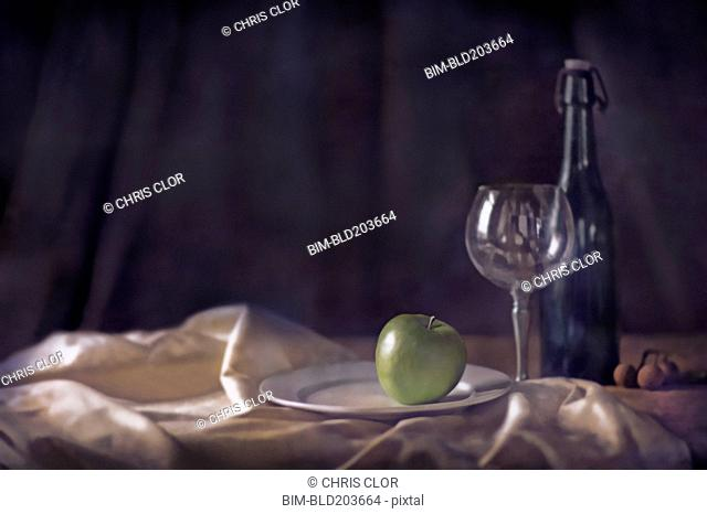 Apple, wine glass and bottle on tablecloth