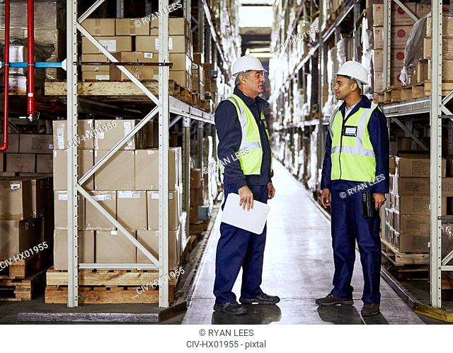 Manager and worker talking in aisle of distribution warehouse