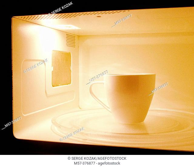 One white coffee mug inside a microwave