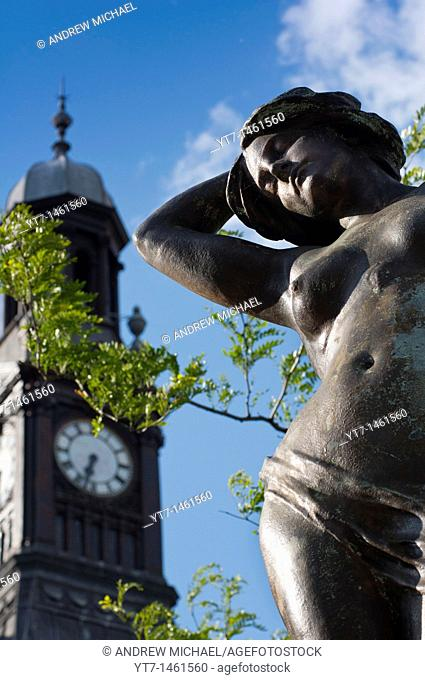 One of the eight Alfred Drury sculpted statues with Old Post office clock, City Square, Leeds, Yorkshire, England