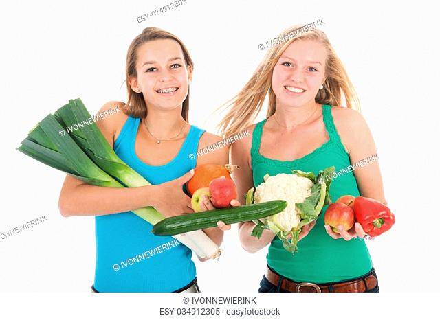 Teen girlfriends with many healthy vegetables and fresh fruit isolated over white background