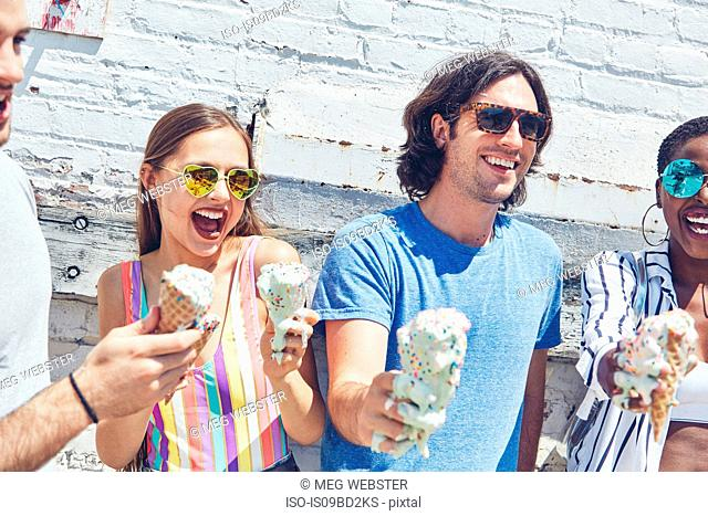 Young women and men holding melting ice cream cones, laughing