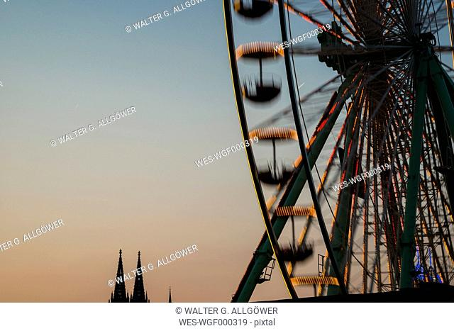 Germany, North Rhine-Westphalia, Cologne, Cologne cathedral and part of big wheel at sunset