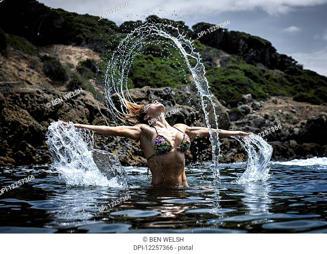 A young woman in a bikini splashing water along the water's edge; Tarifa, Cadiz, Andalusia, Spain