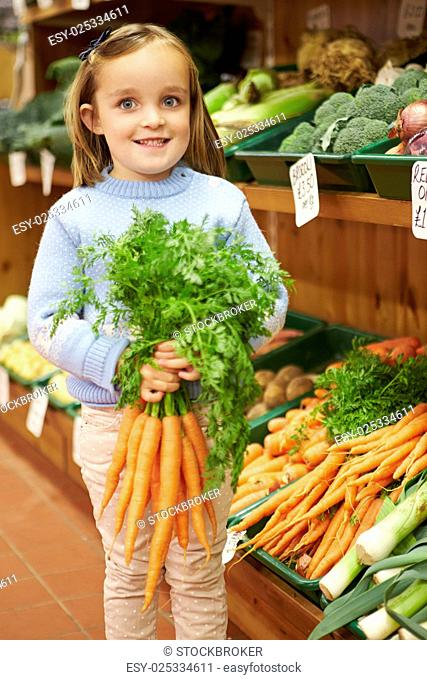 Young Girl Holding Bunch Of Carrots In Farm Shop