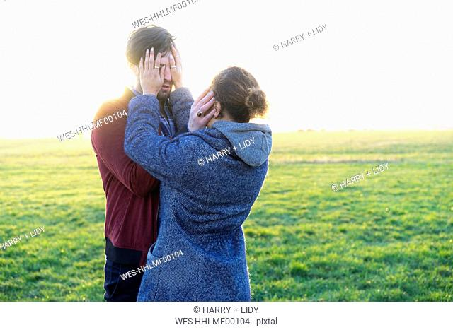 Young couple standing on a meadow covering their eyes
