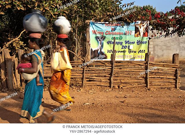 Two tribal women are walking in front of a poster celebrating Christian festivities ( Kandhamal district, Odisha state, India)