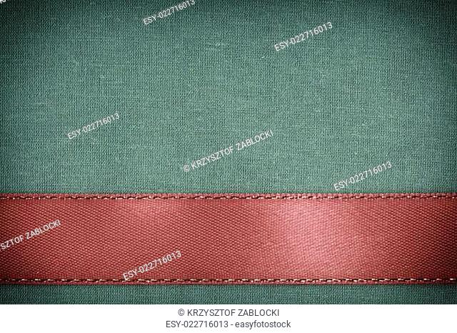 red ribbon on green fabric background with copy space
