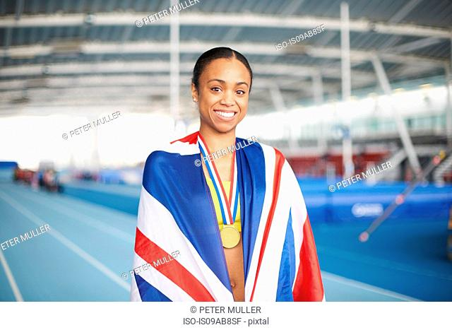 Young female athlete wrapped in UK flag with gold medal