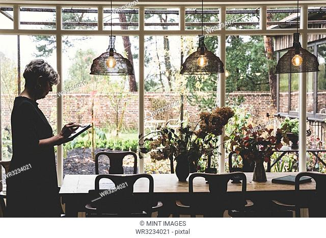 Senior woman wearing glasses and looking at digital table standing in conservatory next to antique wooden dining table and chairs