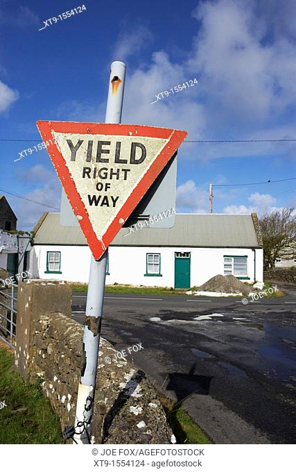 old irish red triangle yield right of way sign in rural ireland