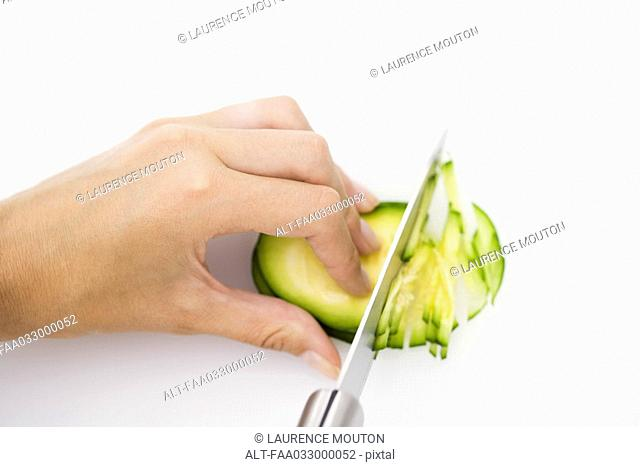 Knife cutting summer squash zapallito redondo, hand holding in place, cropped view