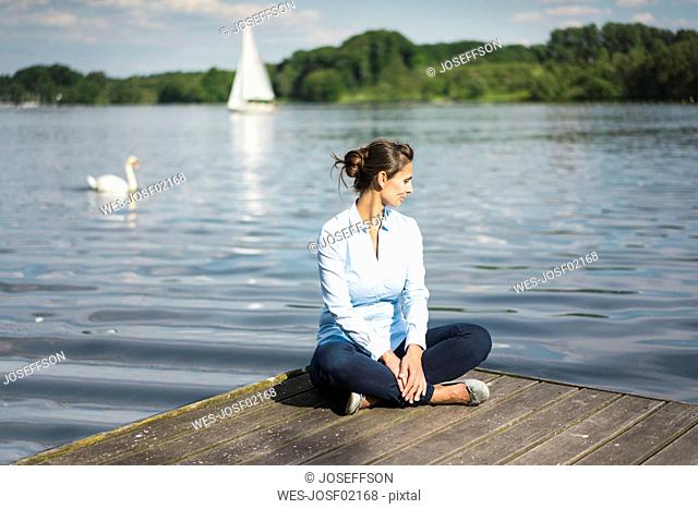 Relaxed woman sitting on jetty at a lake
