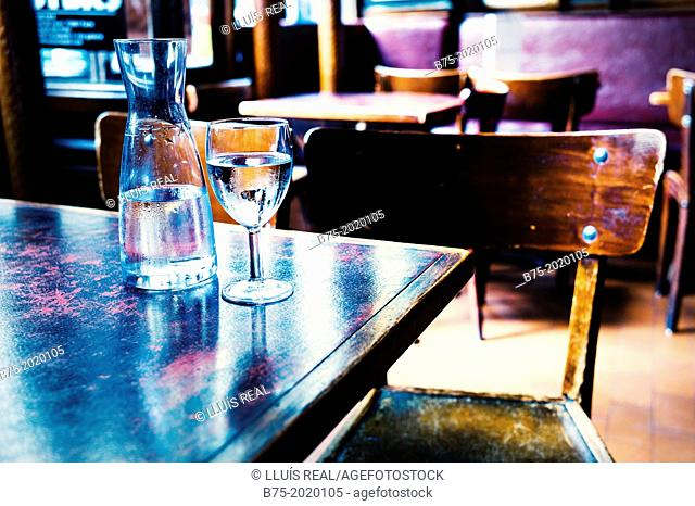 detail of a table with a bottle of water and an empty glass in a typical restaurant of Saint-Germain-des-Prés, Paris, France