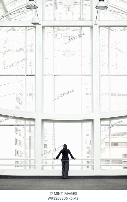 A businesswoman standing at a window in a large convention centre lobby
