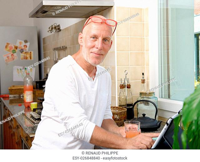 a senior man in kitchen using digital tablet and drink fruit juice