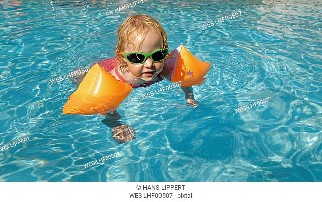 Little girl with water wings in swimming pool