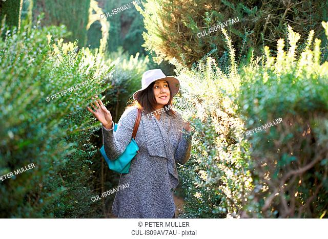 Mature woman wearing sunhat and cardigan touching plants, looking away smiling, Seville, Spain