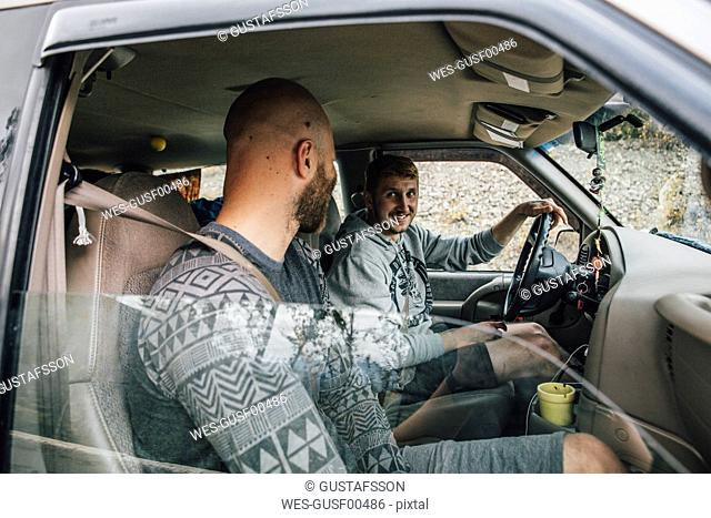 Two smiling young men in car on a road trip