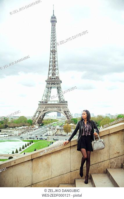 France, Paris, Young woman standing on bridge with theEiffel Tower in background