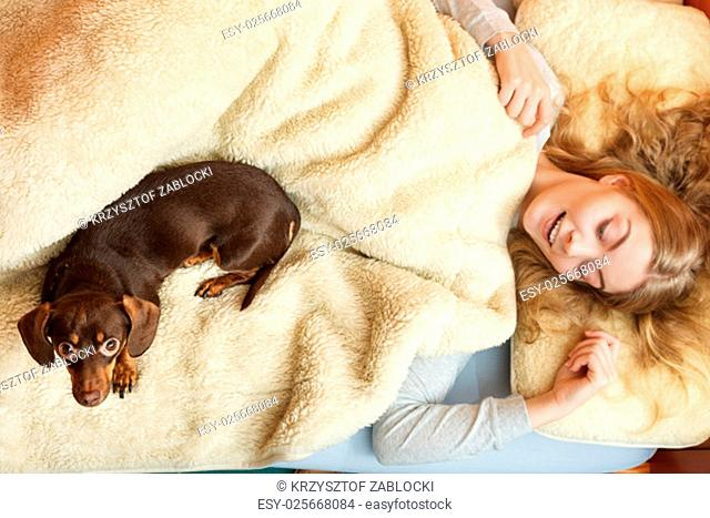 woman with dog waking up in bed in the morning after sleeping. young girl laying under wool blanket