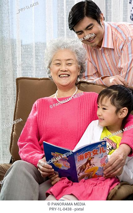 Grandmother,father and daughter reading at home