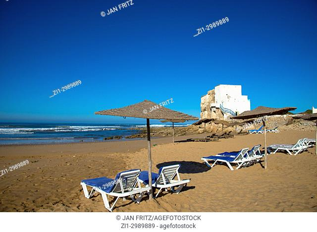 beach with sunbeds and white tower at Sidi Kaouki, Maroc