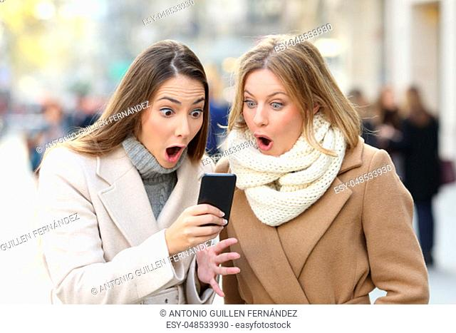 Front view portrait of two surprised women reading phone content in winter in the street