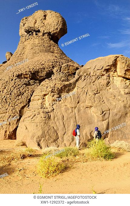 tourists looking at a rockart panel, Youf Ahakit, Tassili du Hoggar, Wilaya Tamanrasset, Sahara Desert, Algeria, North Africa