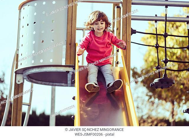 Portrait of little girl sitting on slide at playground