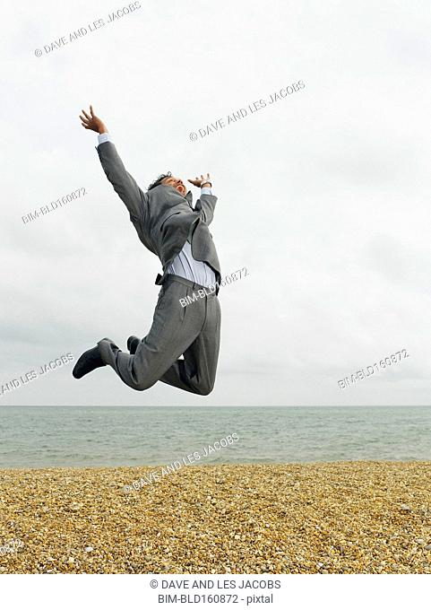 Mixed race businessman jumping for joy on beach