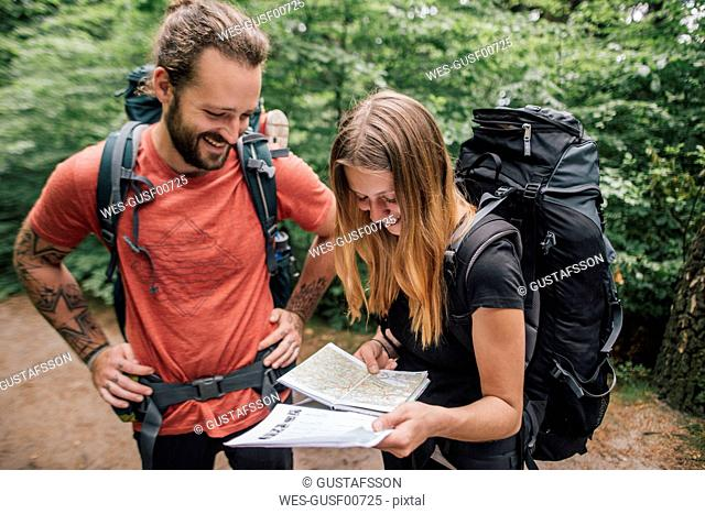 Happy young couple on a hiking trip reading map