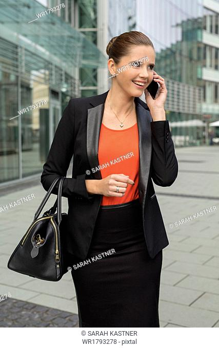 Young businesswoman with cellphone in front of office building