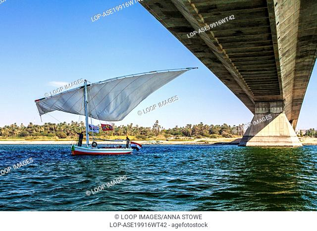Tourist felucca swivels its main sail as it passes under the bridge at Aswan on the Nile in Egypt