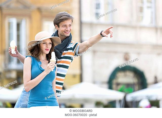 Young couple enjoying ice cream cones during vacation